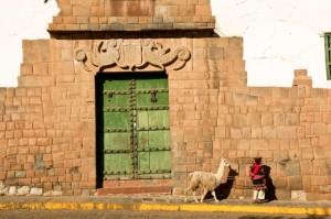 Jauna mergina ir jos alpaka, einančios palei rūmų sieną, dekoruotą inku simboliais. Peru, Cuzco regionas,, Cuzco, Nezaneras aikštė